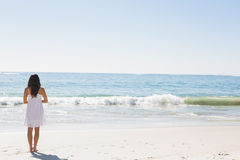 Brunette in white sun dress standing by the water. On the beach Royalty Free Stock Photography