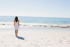 Brunette in white sun dress walking to the sea Royalty Free Stock Images