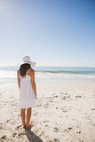 Brunette in white sunhat and dress looking at the ocean Stock Photos
