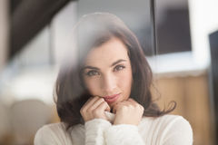 Brunette in white wool jumper smiling at camera Royalty Free Stock Images