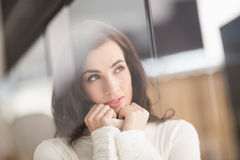 Brunette in white wool jumper thinking Stock Photos