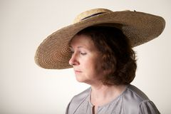 Brunette in wide-brimmed straw hat looking down Royalty Free Stock Image
