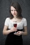 Brunette with a wine glass. On gray background Stock Photo