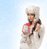A brunette in winter clothes holding a present Stock Photo