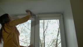 The brunette wipes the ceiling over the plastic window on a spring day. stock footage