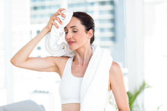 Brunette wiping her forehead with towel royalty free stock photography