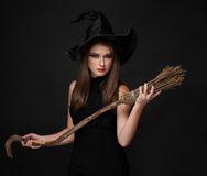 The  brunette witch with a broom in the studio Stock Photos