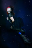 Brunette witch flying on broom Stock Photos