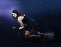 Brunette witch flying on broom Stock Photo