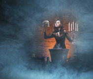 A brunette witch making poison in the dungeon stock images