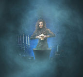 A brunette witch making poison in the dungeon Royalty Free Stock Images