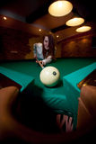 Brunette woman aiming with cue at billiard ball Stock Photos