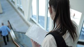 Young woman goes down the escalator at the airport holding documents. Brunette woman with backpack goes down the escalator at the airport holding documents and stock footage