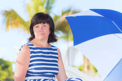 Brunette woman with a beach umbrella Stock Photography