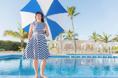 Brunette woman with a beach umbrella Stock Images