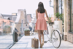 Brunette woman with bicycle. Beautiful brunette woman in pink dress with bicycle and suitcase Royalty Free Stock Photography