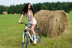 Brunette woman on bicycle in the field Stock Photos