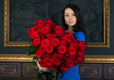 Brunette woman with a big bouquet of red roses. Pretty brunette holding a large bouquet of red roses stock photos