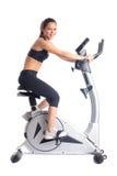 Brunette woman on bike  exerciser Royalty Free Stock Images