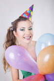 Brunette Woman in a Birthday Cap Holding Balloons and Smile Stock Images