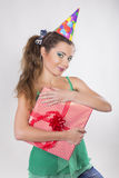 Brunette Woman in a Birthday Cap Holding Presents Royalty Free Stock Photos