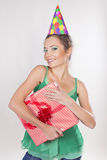 Brunette Woman in a Birthday Cap Holding Presents Royalty Free Stock Images