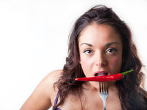 Brunette woman biting a chilli royalty free stock images