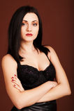 Brunette woman in black dress on the brown background Royalty Free Stock Photo