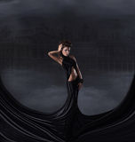 A brunette woman in a black dress on a dark background Stock Photos