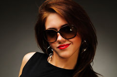 Brunette woman in black dress and glasses Stock Image