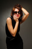 Brunette woman in black dress and glasses Stock Photography