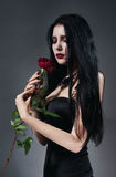 Brunette woman in black dress with red rose Stock Photo