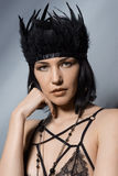 Brunette woman with black feathers on head wearing lacy bra Royalty Free Stock Photography