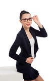 Brunette woman in black skirt and jacket sitting on cube Stock Photography