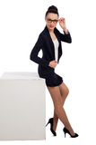 Brunette woman in black skirt and jacket sitting on cube Stock Photos