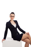 Brunette woman in black skirt and jacket sitting on cube Royalty Free Stock Images