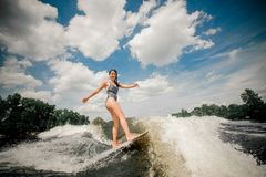 Brunette woman in black swimsuit wakeboarding down the river Stock Image
