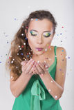 Brunette Woman blow away the confetti on her Birthday Party Stock Image