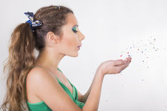 Brunette Woman blow away the confetti on her Birthday Party Stock Photos