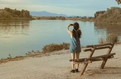 Brunette woman with blue cowboy photographing a river with a mobile stock images