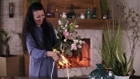 Brunette woman in blue dress, female florist gently ties up ready beautiful bouquet with ribbon. Floristry, handmade. Concept. Fireplace on the background stock footage