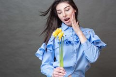 Brunette woman in blue shirt holding yellow flowers in her hands. Closeup portrait of a beautiful happy brunette woman in blue shirt holding yellow jonquils in royalty free stock photos