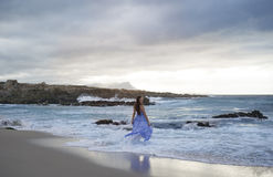 Brunette woman in blue standing in ocean Royalty Free Stock Photos