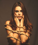 Brunette woman bound with rope prisoner in jeans on a gray backg Royalty Free Stock Image