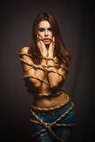 Brunette woman bound with rope prisoner in jeans Stock Photos