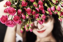 Brunette woman with a bouquet of pink roses Stock Image