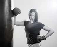 Brunette woman in boxing gloves and body hitting pear. Royalty Free Stock Image