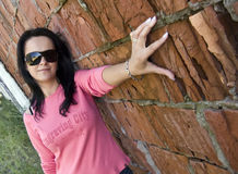 Brunette woman at brick wall Stock Photography