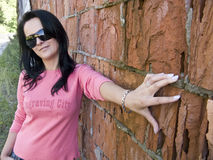 Brunette woman at brick wall. A pretty brunette woman posing at a rough red brick wall Royalty Free Stock Images