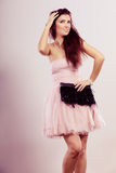 Brunette woman in bright dress with clutch bag Royalty Free Stock Photo